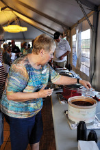 Barb Drury scooping a sample of chili for tasting. undefined