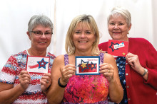 Sally Carstens, Carol Smith and Pricilla Kramer, members of the Paper Crafting Club, proudly showing some of the thank you cards prepared by them and by their fellow club members. undefined
