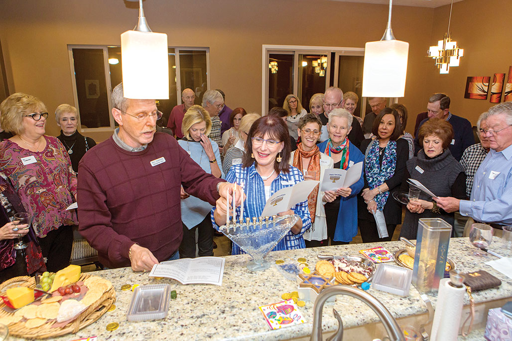 Martha and Bill Sampson leading the lighting of the Hanukkah menorah undefined