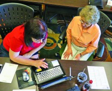Gloria Quigg helps a guest with online research. Photo by Ken Gorman