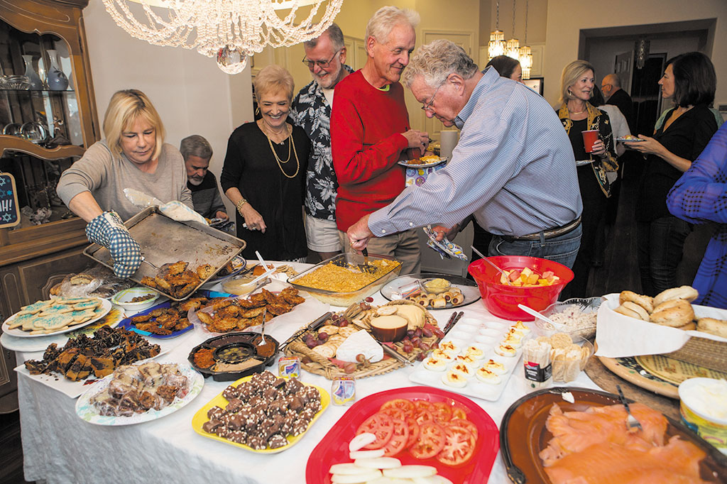 Judi Slavin-Cosel adding more latkes to the lavish buffet of holiday delights. Photo by Steve Weiss