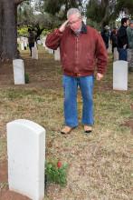 Tom Sorensen of SaddleBrooke Ranch saluting veteran's grave