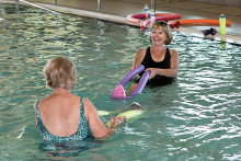 Helga Stone, left, being given special instructions before class by instructor Cathy Lair; photo by Steve Weiss