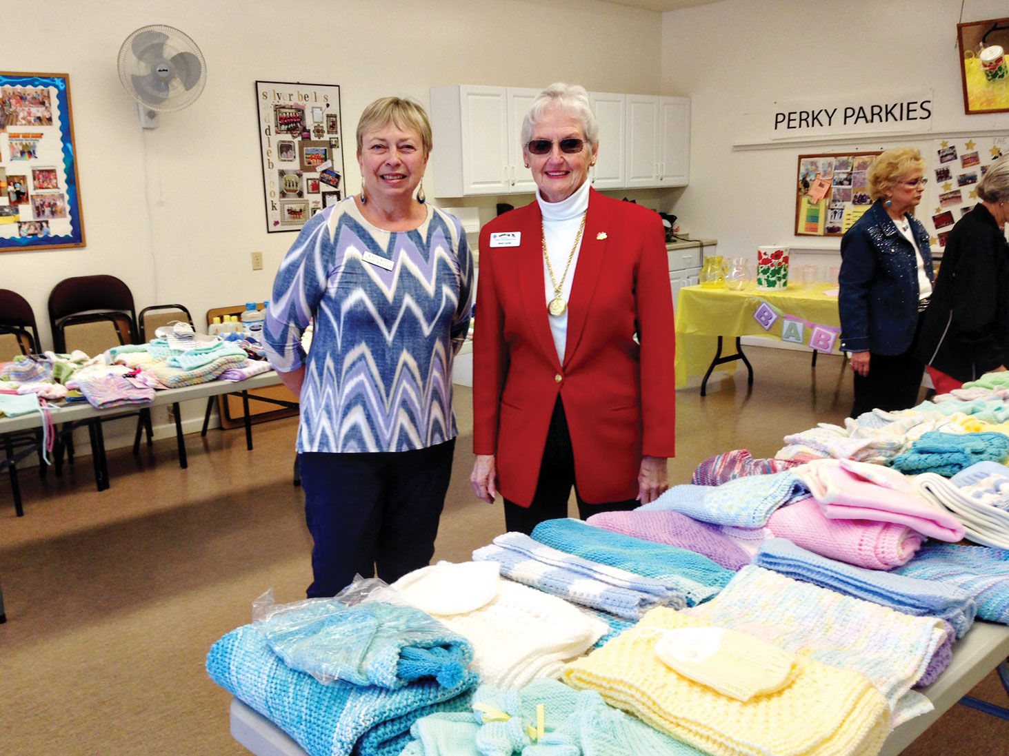 Before…Joan Hansen and Barb Carter help to organize and sort all donated items from the Knit-Wits baby shower for Tucson Troop Support.