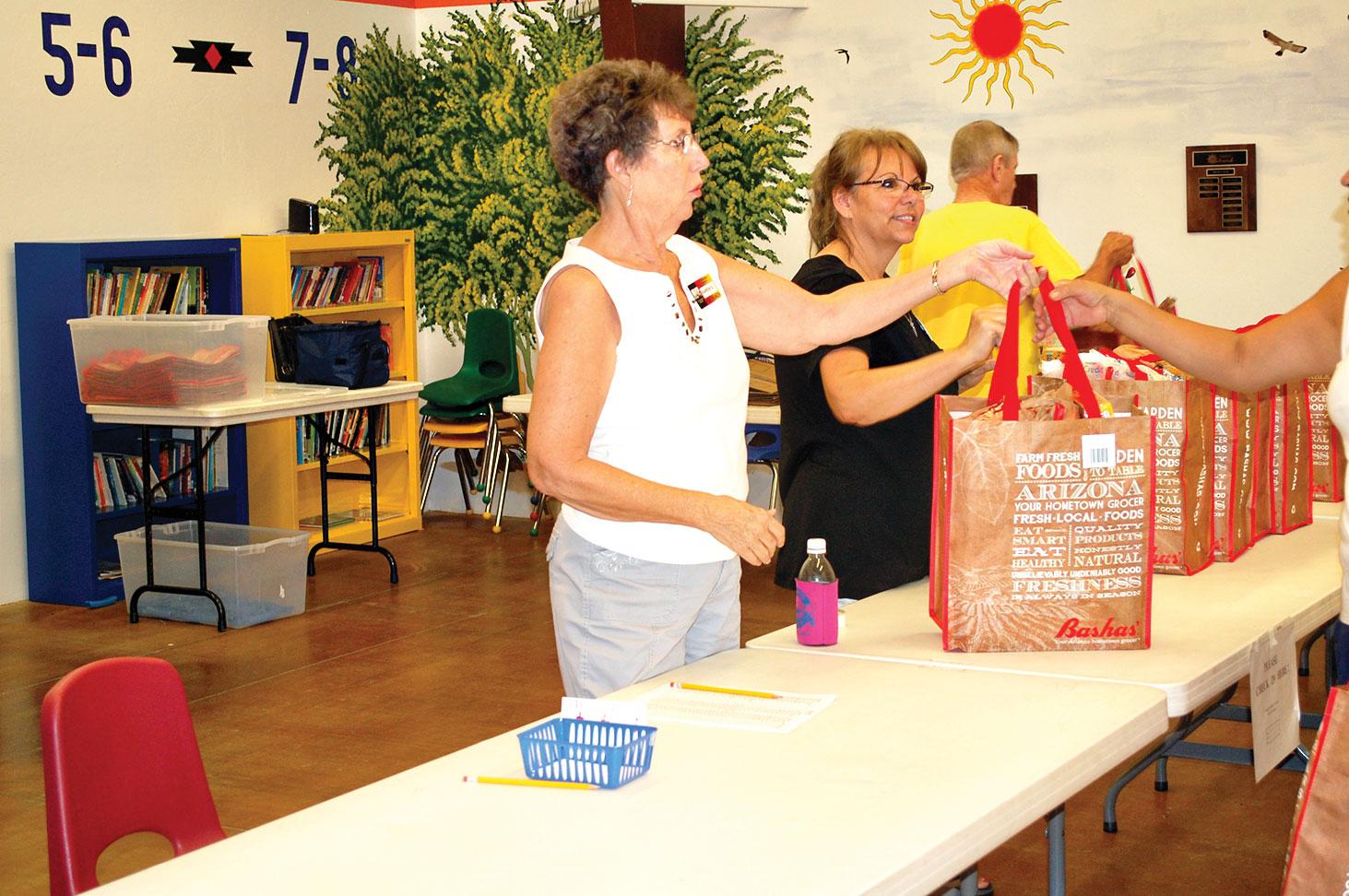 Karen Stott and Terri Kunz with packed bags of food