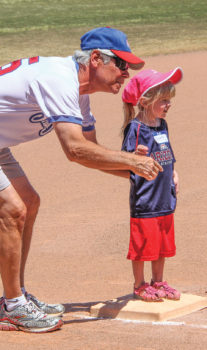Quinn is ready to run home from 3rd base, with encouragement from Grandpa/Coach Terry Mihora. Photo by Jim Smith.