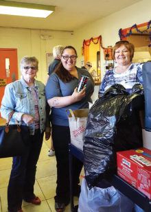 Marian Bianchini and Mary Schlachter deliver the donations to Liz, center, at PACC; photo by Deb Lawson