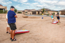 Guy Shelton and Rich Osterland are being shown by their wives Debbie Shelton and Jeanne Osterlund how to play corn bag toss.