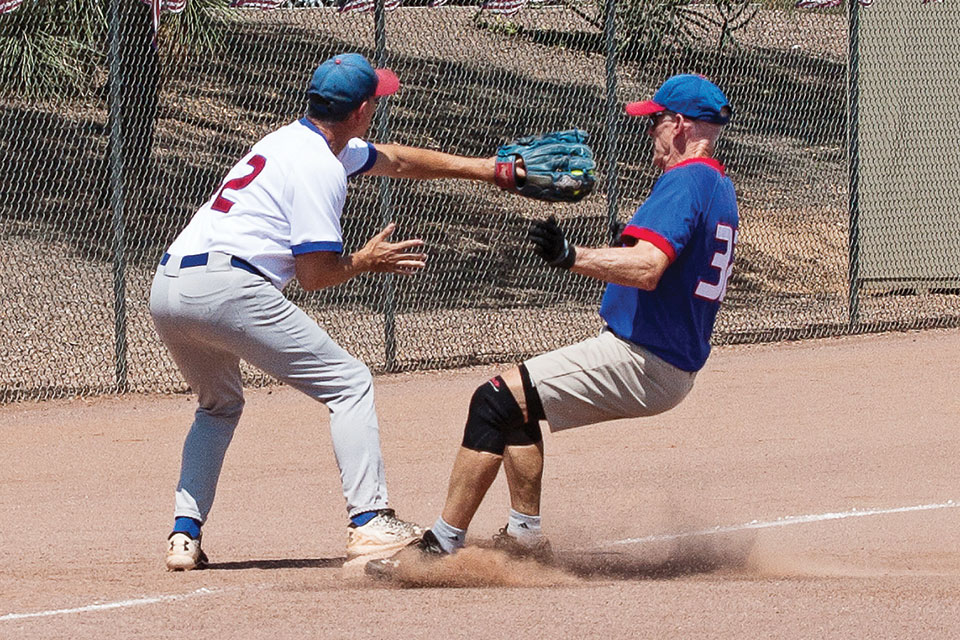 Competitive game: Harold Weinenger reaches to tag runner Don Jones as he stirs up the dust at third base. Photo by Dennis Purcell