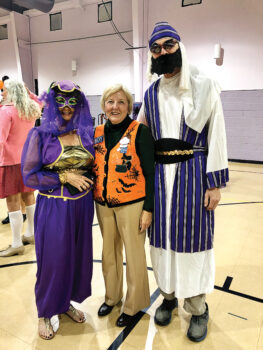 Ranchero Rebecca Williams in Halloween vest flanked by Ted and Ruthie Thoren dressed as a sultan and his lady.