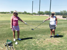 Lisa Brown and Leslie Brown measure proper social distancing before golf.