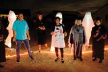 """Creators of many of the evening's props and the Ghost Hosts gather at the Haunted Vacant Ground after the Walking Ghost Tours during Unit 8A's Halloween """"Night of Fright."""" Left to right: Bob Townsend, props creator and carpenter, Ghost Hosts Morbid Mona (Marci Whitehead), Bertha the Butcher (Judie Townsend), Scary Mary (Kate Thomsen), and Francis Fraidy Cat (Janelle Authur)."""