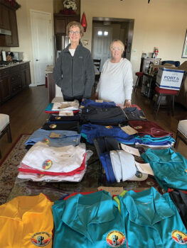 Dian Gowen, Chairman of the Logo Committee, and committee member Julee Malone check and sort the Unit 8A logo clothing items prior to distribution to residents.