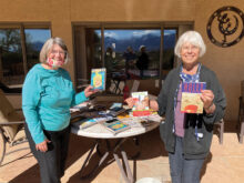 Patty See and Mary Thompson prepare books for teachers' classroom libraries.