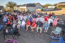 Residents of Unit 8A pose for the traditional group photo, memorializing another year of monthly happy hours. (Photo by Steve Weiss)