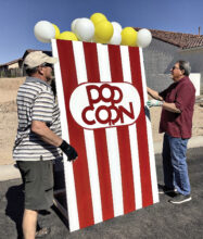 """Stan Doepke and Bob Townsend set up the concession stand popcorn box as the committee decorated for the Unit 8A event """"Drive-In"""" Through the Years. (Photo by Janelle Authur)"""